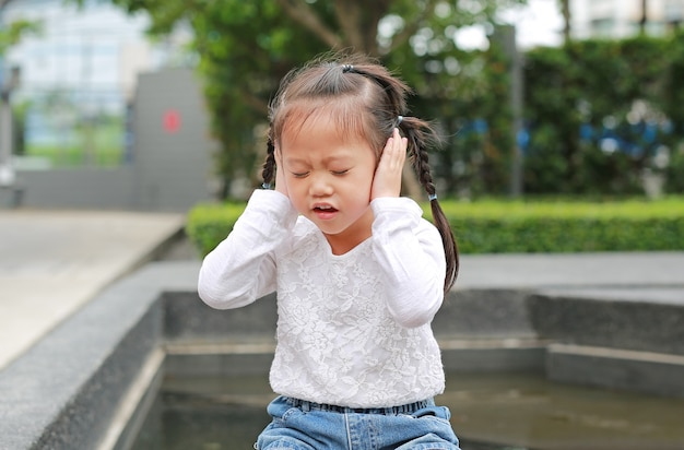 Kid girl holding her hands covers ears not to hear.