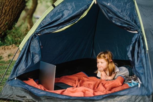 텐트에서 캠페인에 아이 소녀. 자연 속에서 가족 여름 휴가. 어린이 관광. 캠프장에서 텐트에서 노트북을 사용하는 아이. 가제트에 만화를 보는 소녀.