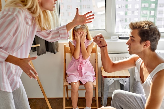 Kid girl is suffering from quarrels between parents in the family at home, woman and man argue in the presence of daughter
