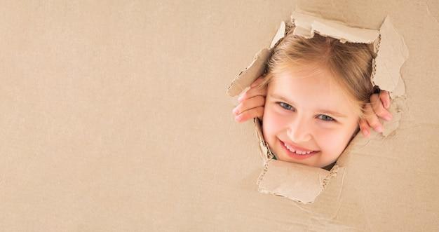 ボックスの穴を通して見る子供の女の子