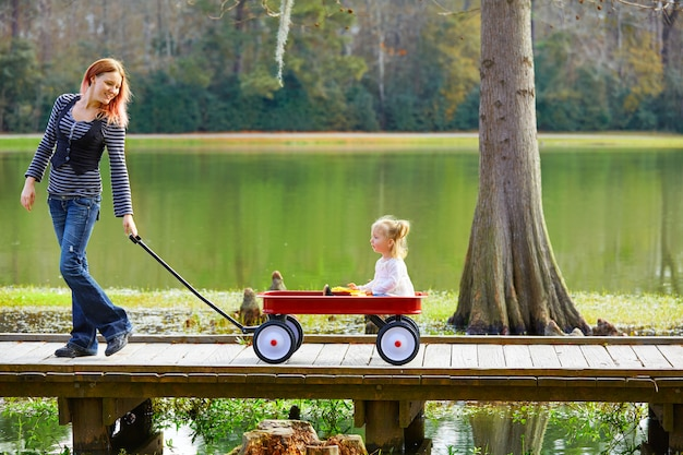 Kid girl and mother walking in lake with pull cart