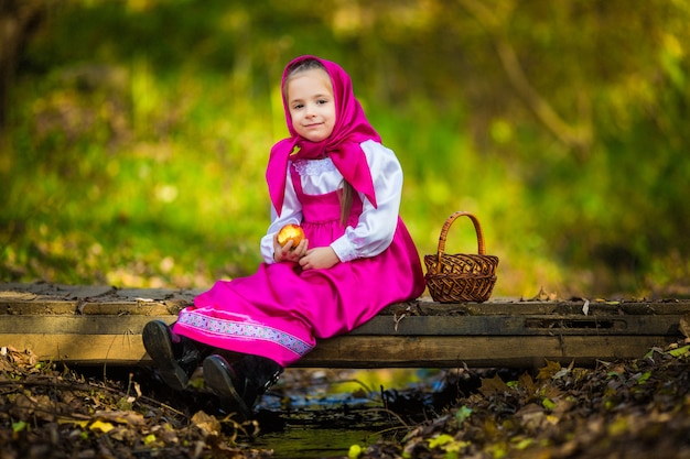 Kid girl in a pink shawl and dress like masha and the bear from the cartoon holds a wicker basket and picks apples.