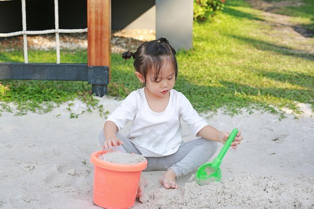 Kid girl playing sand near the beach