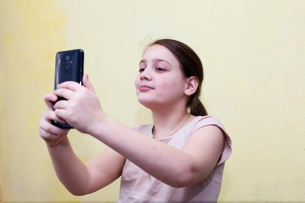 Популярный instagram-блогер kid girl делает селфи на смартфоне
