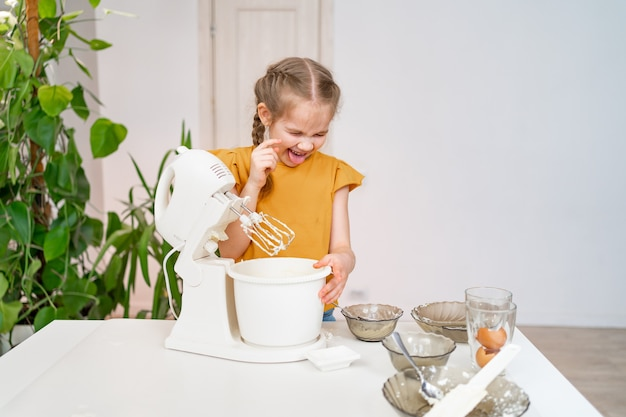 The kid girl prepares dough or cream in a submersible mixer, tries and it tastes unpalatable.