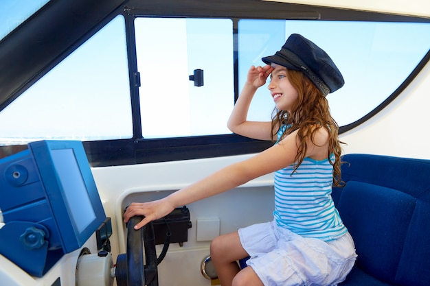 Kid girl pretending be a captain sailor cap in boat