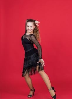 Малыш девушка довольно бальных танцоров носить черное платье в танцевальной позе, танцевальной школе.