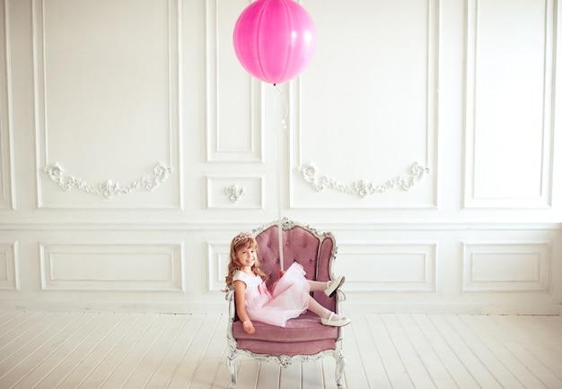ピンクの風船を保持している肘掛け椅子に座っている子供の女の子
