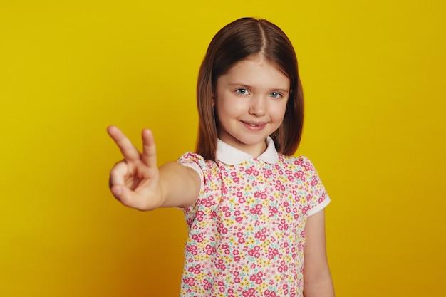 Малыш девушка улыбается, показывая жест мира на желтом фоне студии