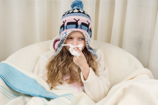 Kid girl sneezes in a handkerchief at home