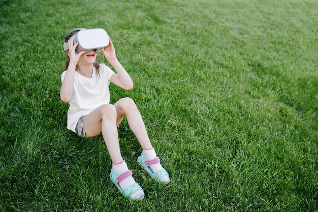 外でバーチャルリアリティメガネを使用して子供の女の子