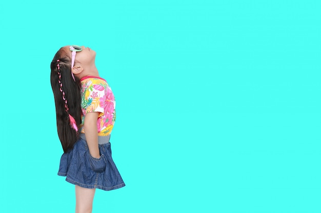 Kid girl wearing a flowers summer dress and sunglasses looking up isolated on cyan with copy space.
