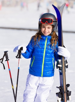 Kid girl winter snow with ski equipment
