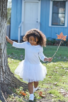 Kid girl with autumn leaf magic wand outdoor