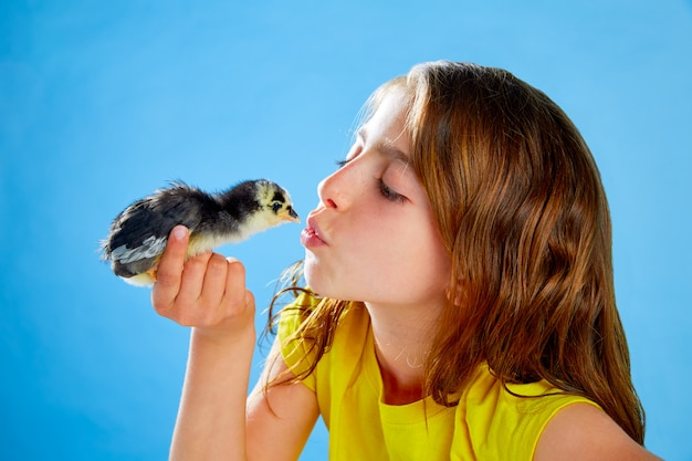 Kid girl with chicks playing on blue
