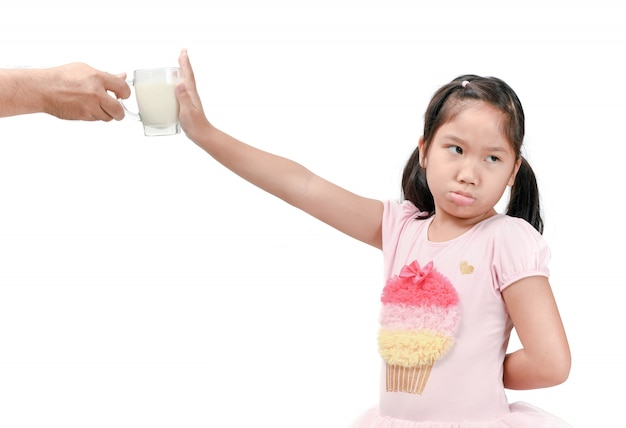 Kid girl with expression of disgust against fresh milk