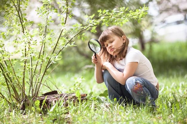 돋보기와 아이 소녀는 잔디를 탐구