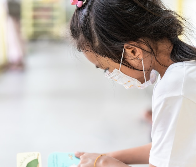 Kid girl with protection mask on in school