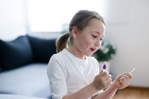 손에 항체 또는 sars-cov-2 바이러스 질병에 대한 테스트 스트립이있는 꼬마 소녀