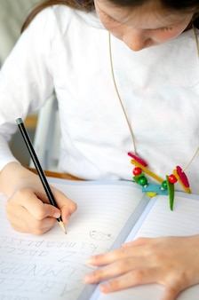 Оягнитесь девушка писать алфавит сидя на домашней таблице во время блокировки вируса короны вниз. обучение на дому и дети в карантине.