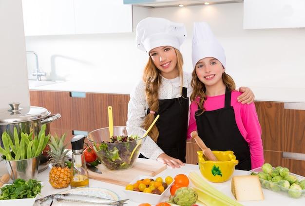 아이 여자 주니어 요리사 친구는 요리 학교에서 함께 포옹