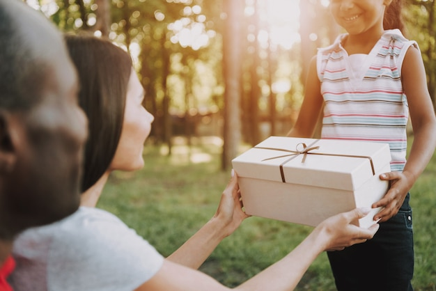 Kid gives present in box to parents on picnic.