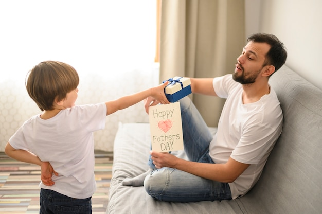 Kid giving present to father