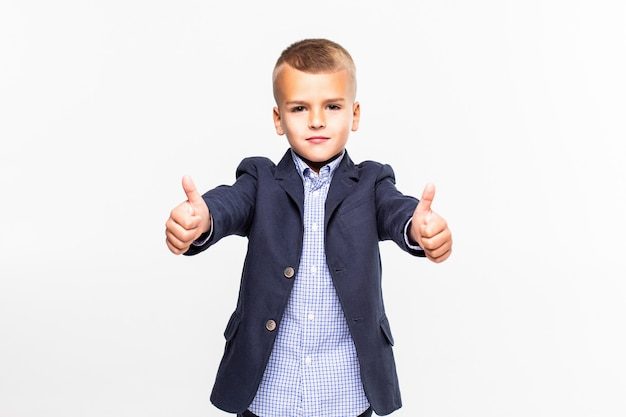 Kid giving thumbs up sign, smiling, isolated on white wall