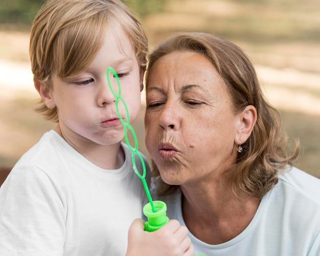 Kid and grandma making soap balloons