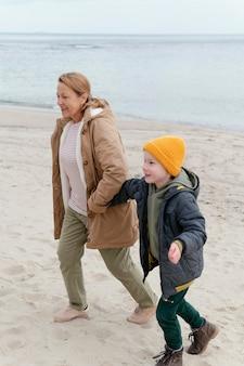 Ragazzo e nonna in spiaggia a pieno colpo
