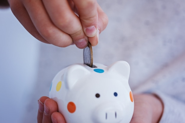 Kid hand putting coin into piggy bank or money box.