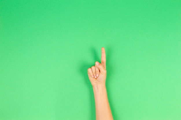Детские руки показаны одним пальцем на зеленом