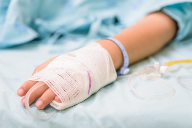 Kid hand sleeps on a bed in hospital with saline intravenous.