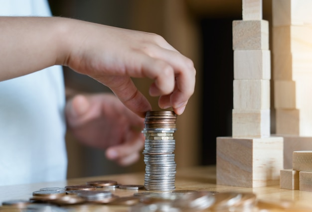 Kid hand stacking sterling pound coin and pennies nickels on wooden table with copy space