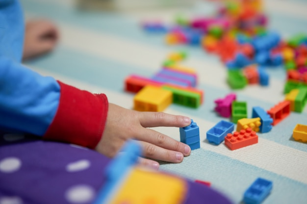 Kid hand touch colorful bricks toy on mat floor for playing
