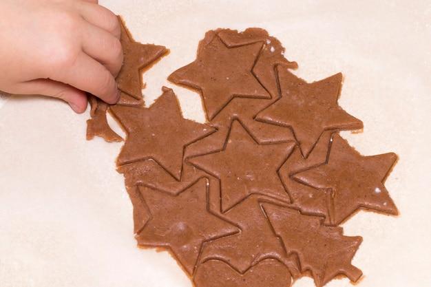 子供の手は、木製のテーブルで生の生地からクッキーをカットします。クリスマスのクッキーと食べ物のコンセプト。