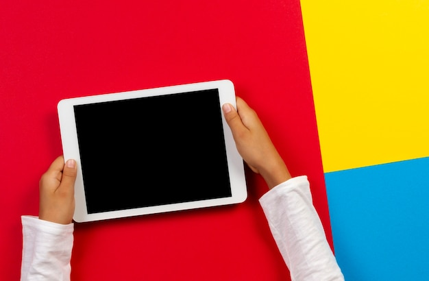 Kid hands holding digital tablet computer on red, yellow and blue background. top view