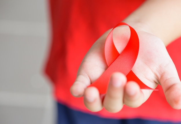 Kid hands holding red aids awareness ribbon. aids awareness campaign