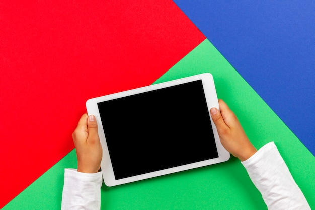 Kid hands holding white tablet computer on light green, blue and red table.
