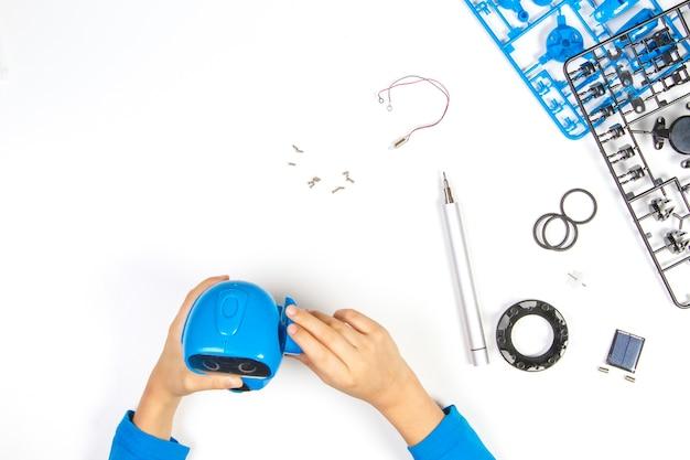 Kid hands making blue robot on white desk.