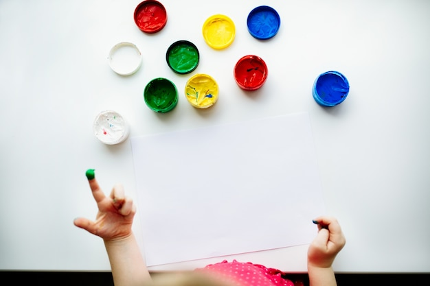 Kid hands start painting at the table with art supplies, top view