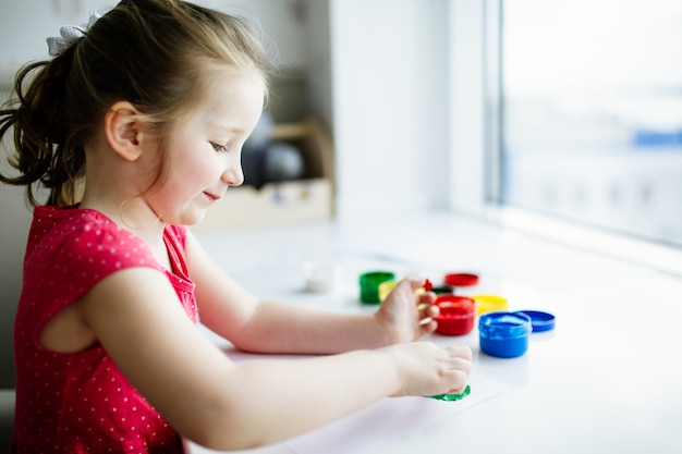 Kid hands start painting at the table with art supplies
