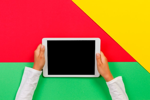 Kid hands with tablet computer on red, yellow and green background