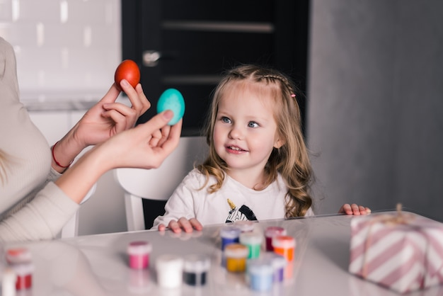 Kid having fun while painting easter eggs in the kitchen