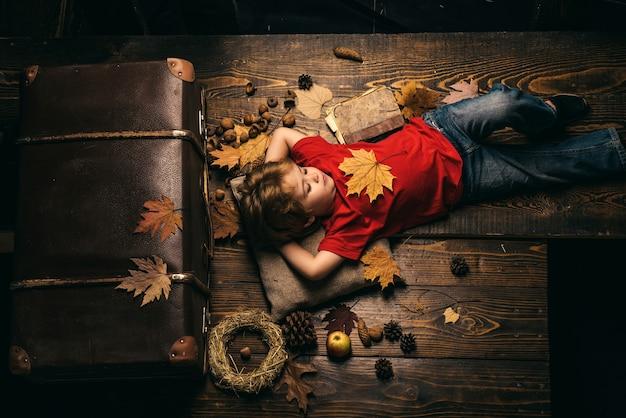 Малыш веселится с листопадом ребенок играет осеньюблондинка маленький мальчик отдыхает с листом на животе ...
