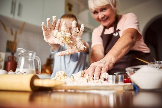 할머니와 요리하는 동안 반죽을 만드는 재미 아이