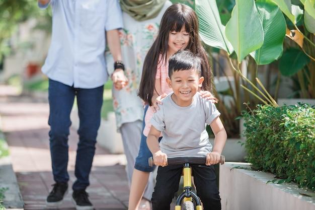 自転車に乗って妹と楽しんでいる子供