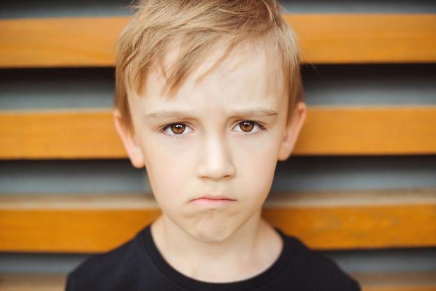 不機嫌そうな不満の表情を持つ子供。子供が悪い行動のために両親に根拠を与えられている。悲しい感情的な少年。