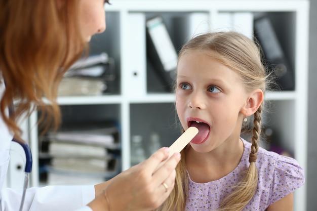 Kid having throat examination with tongue depressor in hospital