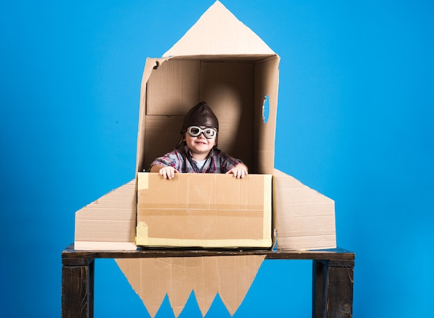 Kid in helmet and pilot glasses sit in cardboard rocket childhood concept happy boy play astronaut